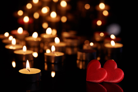 Two decorative hearts  and burning candles on a black background with reflection. Valentine's Day card. Design element for romantic greeting card, wedding invitation, Banco de Imagens