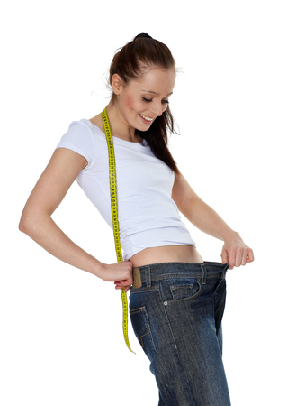 The beautiful young woman in old jeans after losing weight on a white background. Concept of healthy lifestyle.