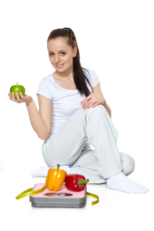 Sporty young woman with scales, fresh peppers and apple on a white background.  Concept of healthy lifestyle. 스톡 콘텐츠