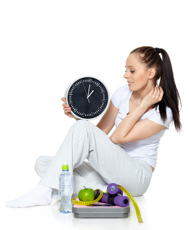 Sporty young woman with clock, scales, dumbbells and apple on a white background.  Time for slimming. Stockfoto