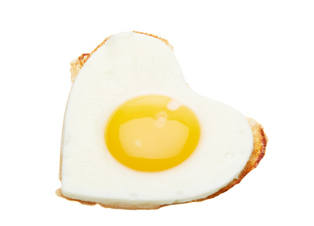 Fried egg in the shape of a heart isolated on a white background. Top view.