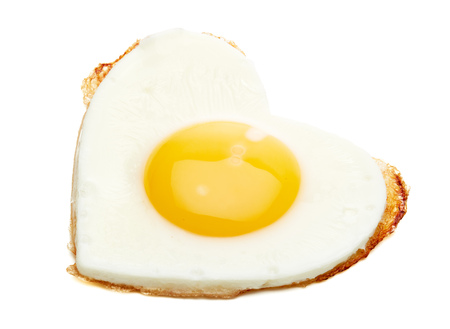 Fried egg in the shape of a heart isolated on a white background. Stock fotó