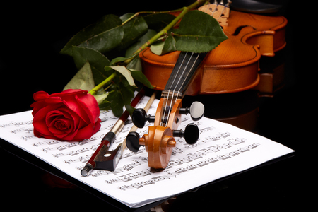 St.Petersburg, Russia - November 2016 - Violin (fiddle) with red rose lying on the sheet of music on a black background. String instrument.