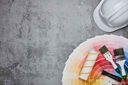 White construction helmet ( hard hat), color palette guide, paint brushes and roller on grey background. Top view with copy space,  Concept of construction or design office
