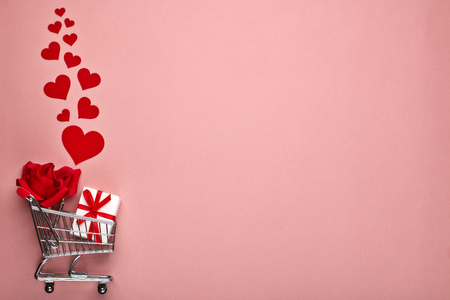 Shopping trolley, gift box, flower and decorative red hearts on pink background with copy space. Valentine's day, Mother's day,  wedding Stockfoto