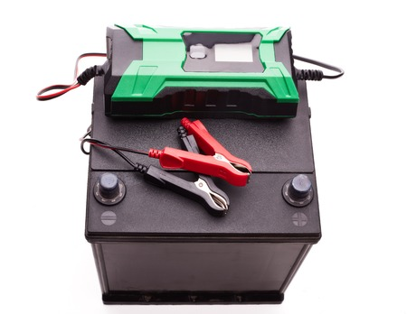 Black car accumulator battery and green charger  isolated on a white background. Top view. Acid battery,12 volts supply. Concept of service, maintenance, charging car battery, diy
