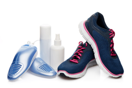 Sports shoes care. Electric shoes dryer with UV sterilization on a white background,  Deodorant for shoe and antifungal agent. Shoe care products. Concept of healthy feet. Fitness and sport footwear