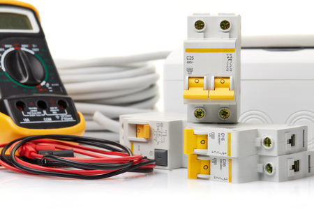 Automatic circuit breakers, distribution box, cable and digital tester on a white background. Electrical equipment. Accessories for electrical  protection and control