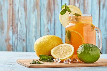 Citrus lemonade with ice, leaves of mint, lemon and lime slices standing on blue wooden table. Homemade lemonade with citruses. Healthy cool beverage