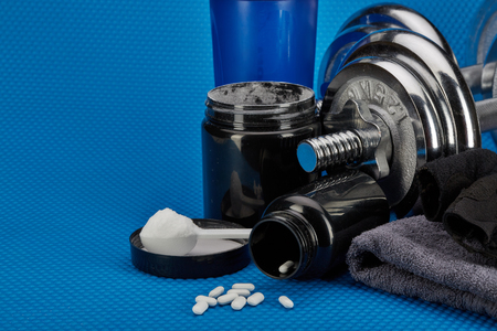 Sports  nutrition (supplements), dumbbells and sports accessories on a blue background. Fitness, bodybuilding, sport and healthy lifestyle concept. Imagens