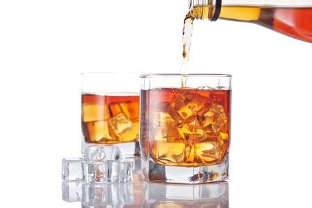 Pouring whiskey from a bottle into glasse with ice standing on a white background with reflection Reklamní fotografie