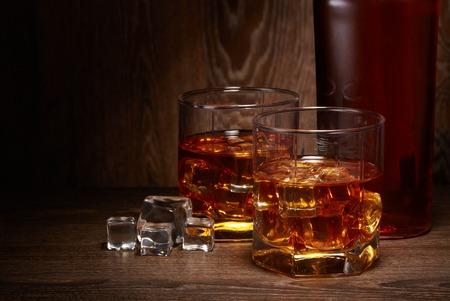 Flasche Whisky und zwei Gläser Whisky mit Eis, die auf einem Holztisch auf dunklem Hintergrund mit Kopienraum stehen.