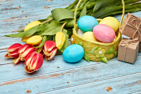 Colored easter eggs in basket, gift boxes and spring tulips flowers on a wooden  background. Top view. Greeting card. Easter background,