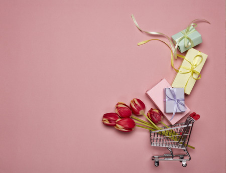 Shopping trolley, gift boxes, tulips flowers on a pink background. Top view with copy space. Valentines day, Mothers day, Womens day, wedding and other festive events. Seasonal sale