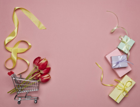 Shopping trolley, gift boxes, tulips flowers on a pink background. Top view with copy space. Valentine's day, Mother's day, Women's day, wedding and other festive events. Seasonal sale