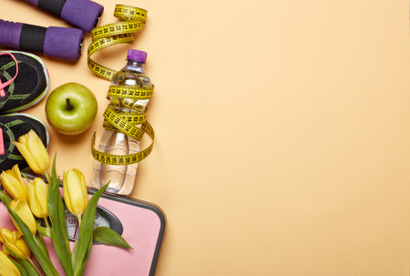 Female fitness still life. Sport accessories, tulips flowers and scales on a yellow background. Mockup. Planning of diet and trainings. Top view with copy space. Healthy lifestyle concept. Slimming
