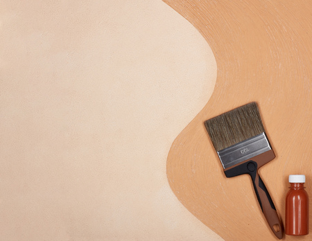 Paint brush and bottle of paint lying on textural double background consisting of two beige shades. Top view with copy space, Concept of construction or design office