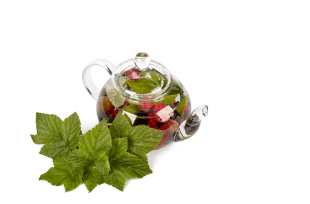 Teapot with fruit tea and green leaves over white background