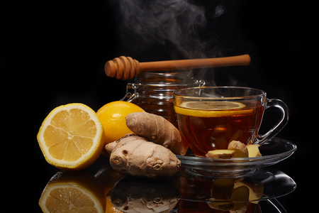 Honey in glass pot and cup of tea with ginger and lemon on a black background.