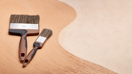 Paint brushes on textural double background consisting of two beige shades. Top view with copy space, Concept of construction or design office