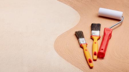 Gele verfborstels en rode roller liggend op een dubbele textuurachtergrond bestaande uit twee beige tinten. Bovenaanzicht met kopieerruimte, concept van bouw- of ontwerpbureau
