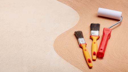 Yellow paint brushes and red roller lying on textural double background consisting of two beige shades. Top view with copy space, Concept of construction or design office Stockfoto