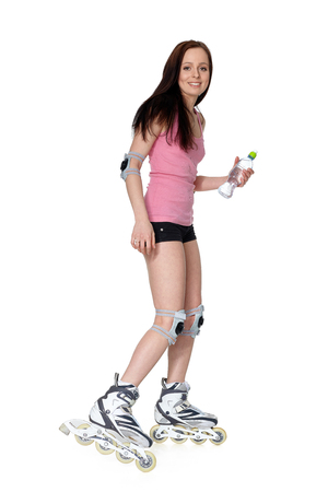 The beautiful young woman in rollerskates on a white background. Stockfoto
