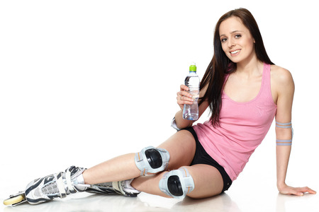 The beautiful young woman in rollerskates on a white background.