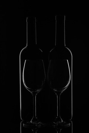 Silhouette of two wine bottles and two empty wineglasses on a black background with reflection. Contour with gradient and highlights
