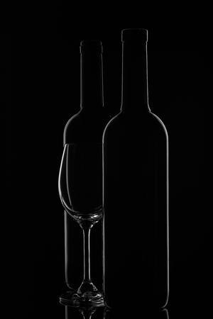 Silhouette of two wine bottles and empty wineglass on a black background with reflection. Contour with gradient and highlights