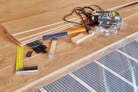 Installation Infrarot-Carbon-Heizfolie für den Boden. Verlegen von fertigem Laminatboden auf einem wärmegedämmten Boden. Elektrische Fußbodenheizung, Strahlungsheizung