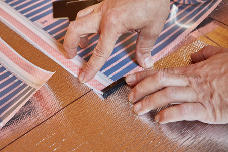 Installation infrared carbon heating film for floor. Male hands are insulating edge of heating film roll using bitumen insulation . Electrical floor heating system, radiant heating