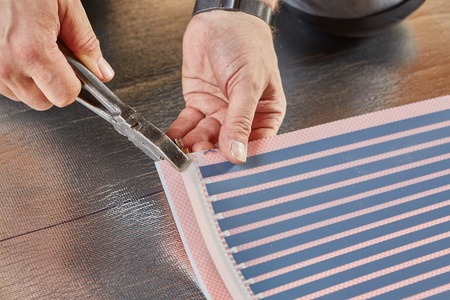 Installation infrared carbon heating film for floor. Male hands are fastening the contact clip to heating film roll. Electrical floor heating system, radiant heating Reklamní fotografie