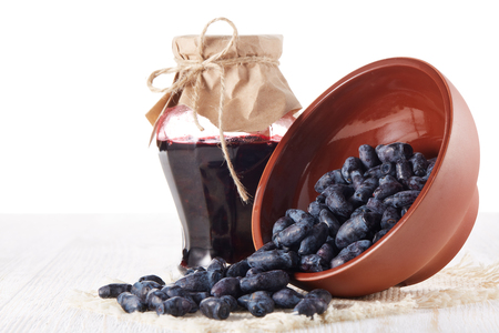 Honeysuckle berries in a ceramic bowl  and glass jar of jam stand  on a wooden table on white background.