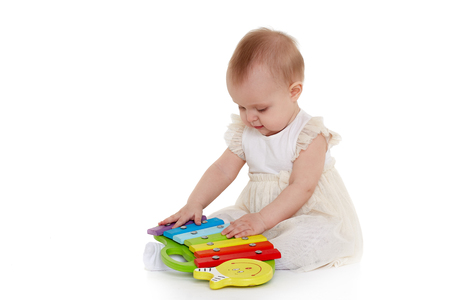 Sweet baby in dress plays with colourful xylophone (musical instrument toy for children) on a white background. Early development and learning toys. Eight months