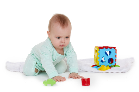 Dulce bebé vistiendo un mameluco verde juega con juguetes para niños sobre un fondo blanco. Juguetes de desarrollo y aprendizaje temprano. Ocho meses Foto de archivo