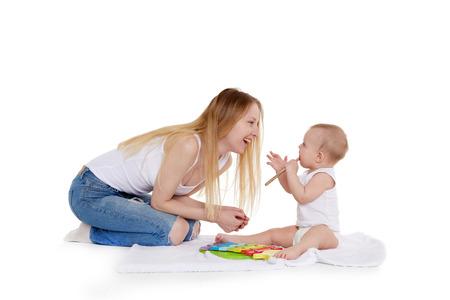 Mujer joven y su hija están jugando con el desarrollo de juguetes musicales sobre un fondo blanco. Familia feliz. Ocho meses