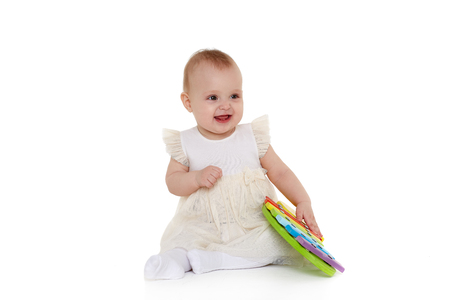 Sweet baby in dress  plays with colourful  xylophone (musical instrument  toy for children) on a white background. Early development and learning toys. Eight months Banque d'images