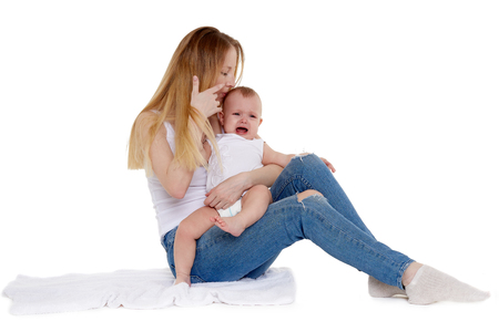 Young mother with unhappy crying baby sit on a white background. Nursing and parenting. Eight months