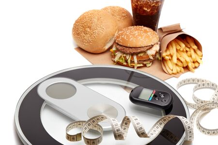 Fast food, medical device  blood glucose meter, scales and measuring tape on a white background. Concept of unhealthy diet and health. Stock Photo