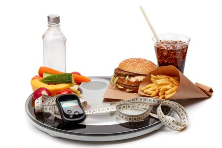 Still life with good and bad food, scales, measuring tape and blood glucose meter on white background. Concept of choice: Fast food or healthy food.  Diabetes