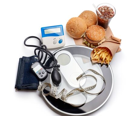 Fast food and medical devices tonometer (blood pressure measuring device) and blood glucose meter, scales and measuring tape on a white background. Concept of unhealthy diet and health.