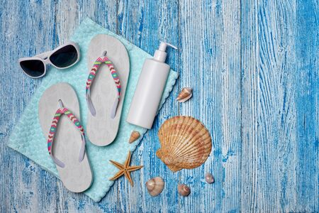 Beach accessories: white female flip flops, sunglasses, sunscreen on blue wooden background. Top view with copy space. Concept of sea vacation and travel. Summer background, Protection from uv 版權商用圖片
