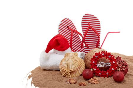 Still life with beach accessories (flip flops, towel, seashells, sand, coconut) and christmas ornaments on white background. Christmas. Winter  vacation  in warm countries, beach holiday