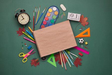 Accesorios de papelería y libros de escritura en blanco: lápices, bolígrafos, otros materiales de oficina sobre fondo verde. Vista superior, espacio de copia. Accesorios escolares para la educación y el desarrollo de los niños Foto de archivo