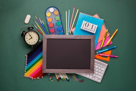 Blank blackboard and stationery accessories: pencils, pens, other office supplies on green background. Top view, copy space.  School accessories for childrens  education and development 版權商用圖片
