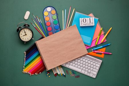 Blank writing-book, computer keyboard, stationery accessories: pencils, pens, other office supplies on green background. Top view, copy space.  School accessories for  education and development 版權商用圖片