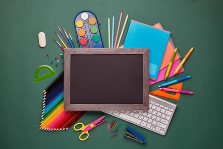 Blank blackboard, computer keyboard, stationery accessories: pencils, pens, other office supplies on green background. Top view, copy space.  School accessories  for education and development