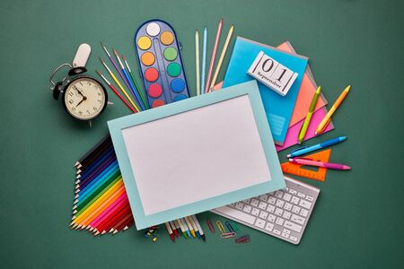 Blue frame with blank sheet, computer keyboard, stationery accessories: pencils and other office supplies on green background. Top view, copy space.  School accessories  for education and development Stockfoto - 128619001