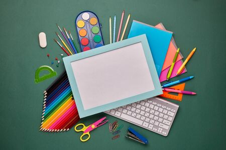 Blue frame with blank sheet, computer keyboard, stationery accessories: pencils and other office supplies on green background. Top view, copy space.  School accessories  for education and development